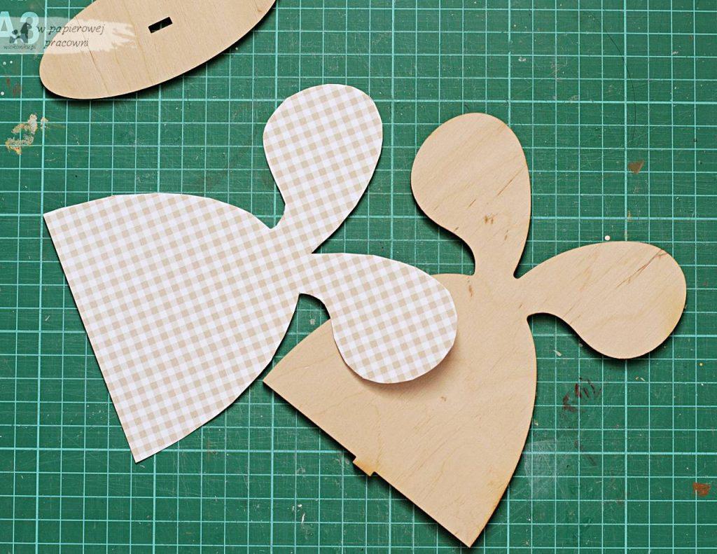 Naklejanie wyciętych elementow z papieru na zajaca ze sklejki