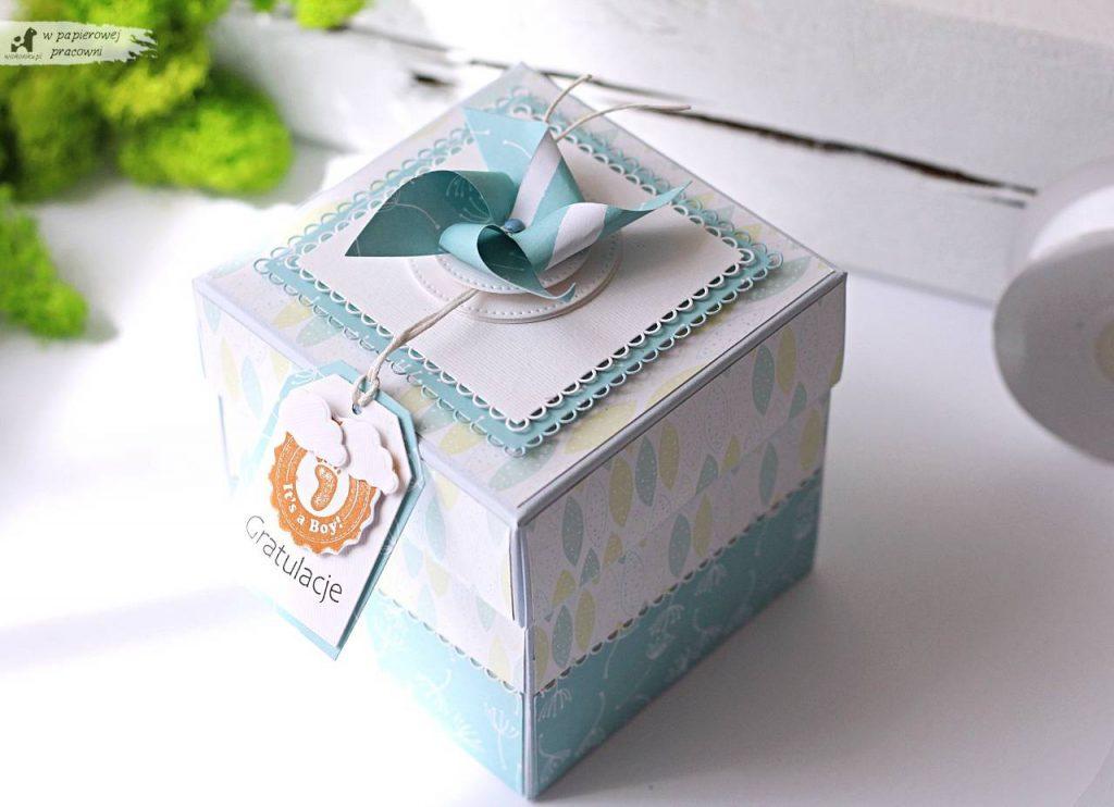 Box z zewnątrz bardzo prosto zdobiony, na wieczku wiatraczek i zawieszka.