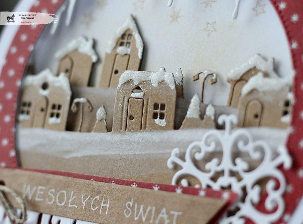 Zbliżenie na ośnieżone domki we wnętrzu kartki świątecznej w kształcie bombki