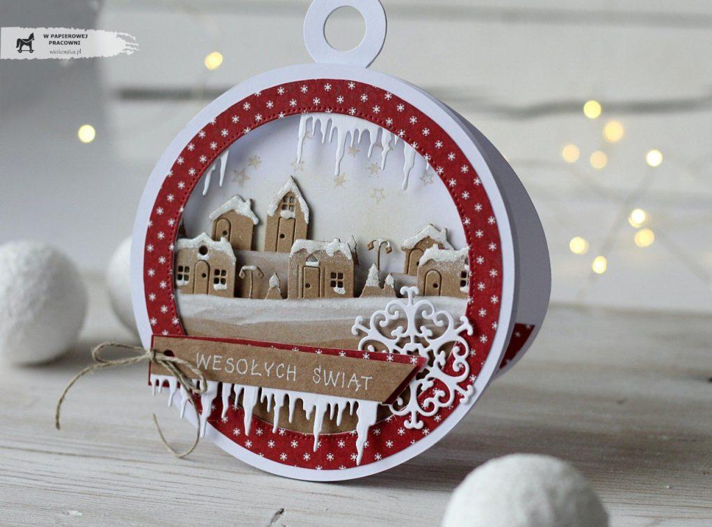 Świąteczna kartka w kształcie bombki z widokiem ośnieżonych domków.