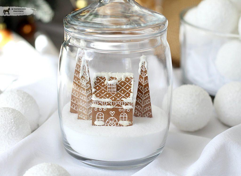 Zimowa scenka zamknięta w słoiczku jako dekoracja świąteczna- papierowy domek i choinki imitujące pierniczki